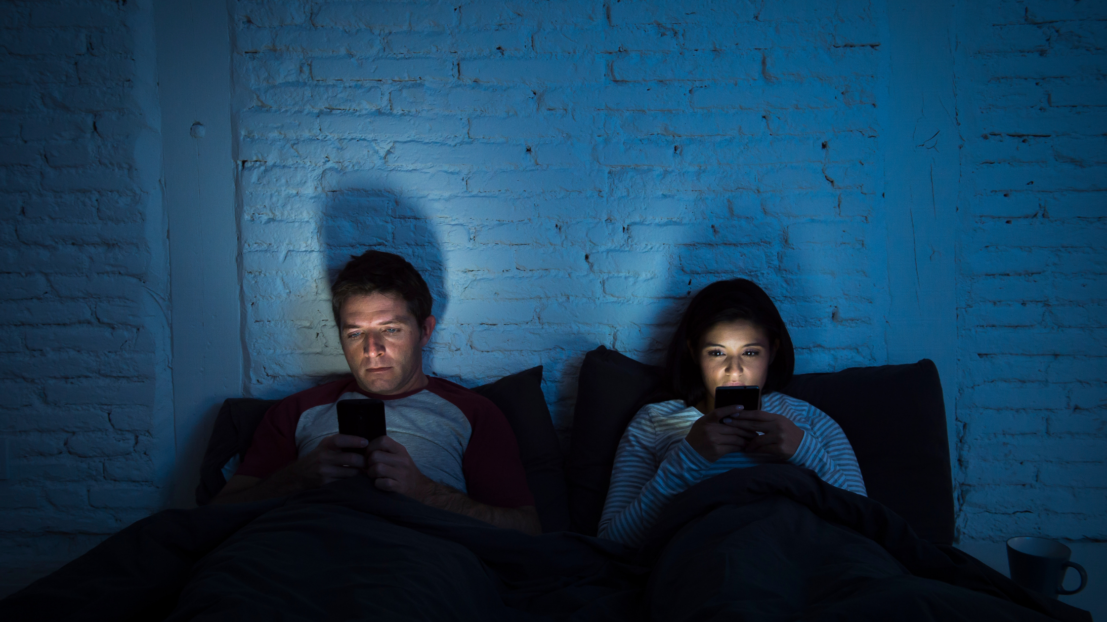 A man & woman lying in bed both on their phones with the screens lighting their faces |Manage Bedtime Revenge Procrastination