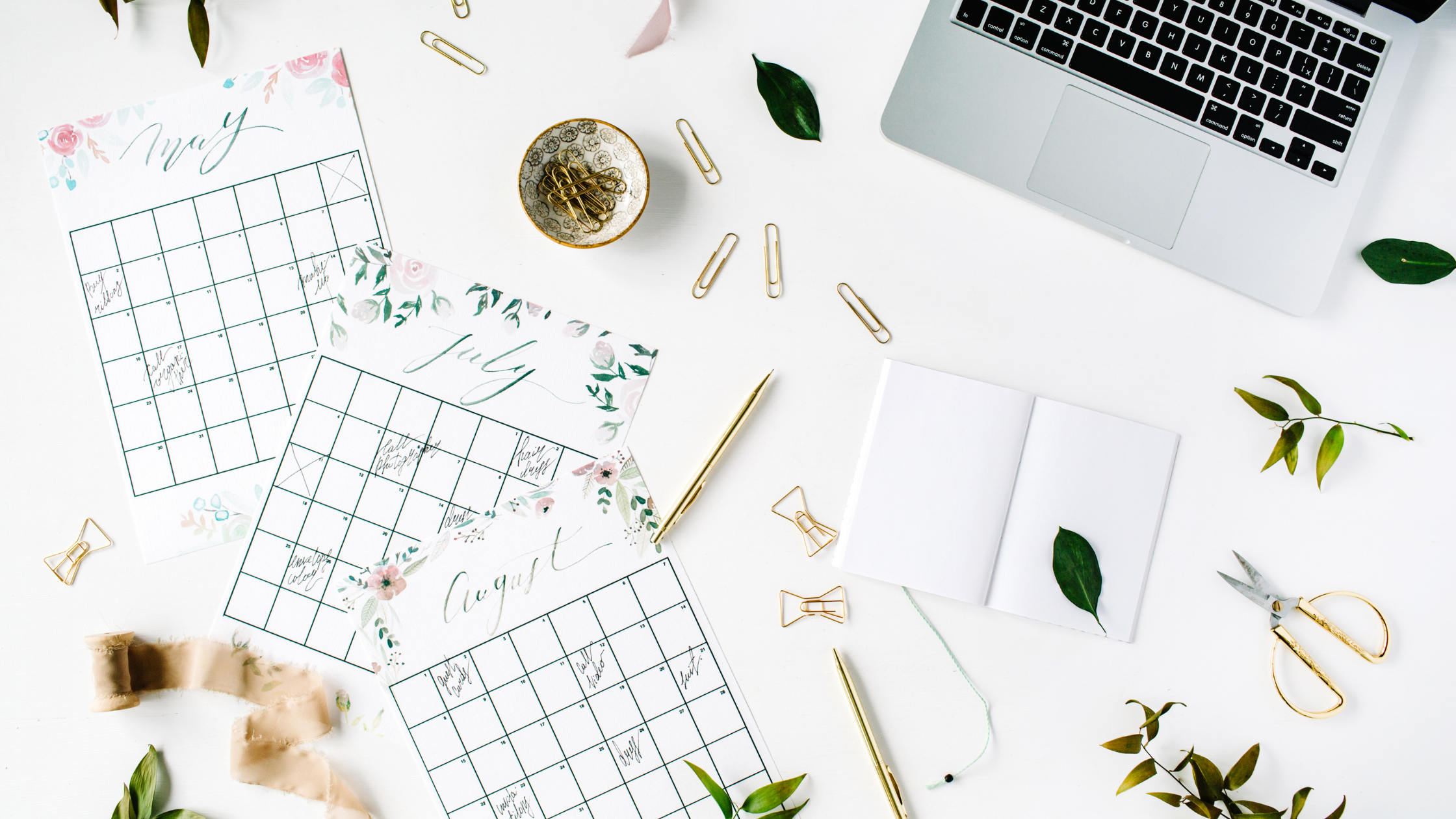 Calendars on a white desk with a laptop, paperclips & greenery. Design your Work Week with Work-Life Boundaries